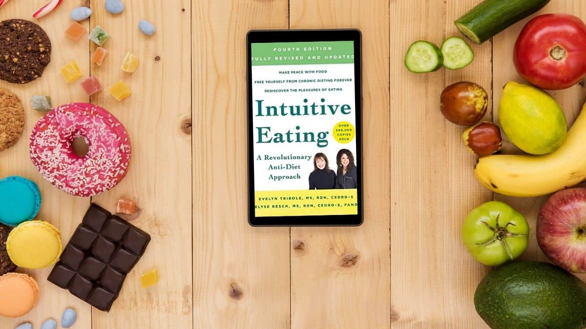 Food on a table with an e-book of the intuitive eating book.