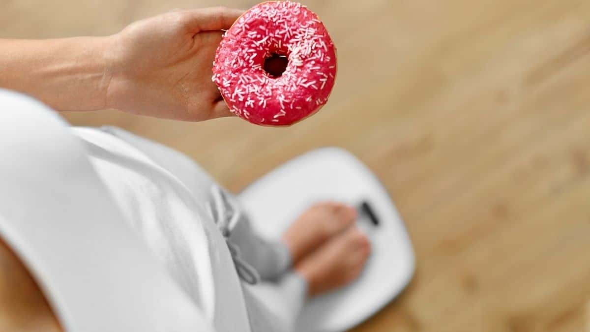 a woman holding a donut while standing on a scale.