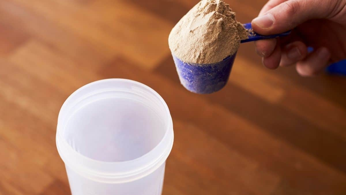 A pink scoop of powder being mixed into a protein meal replacement shake cup.