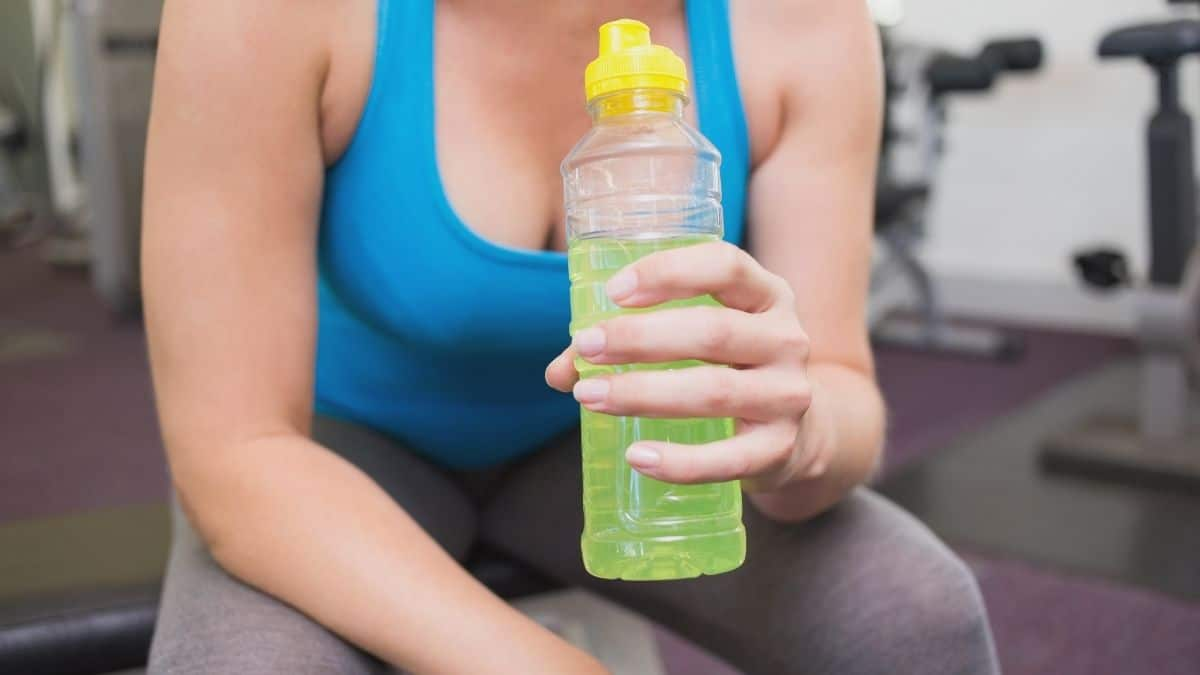 A woman in a blue tank top holding a waterbottle filled with a keto energy drink.