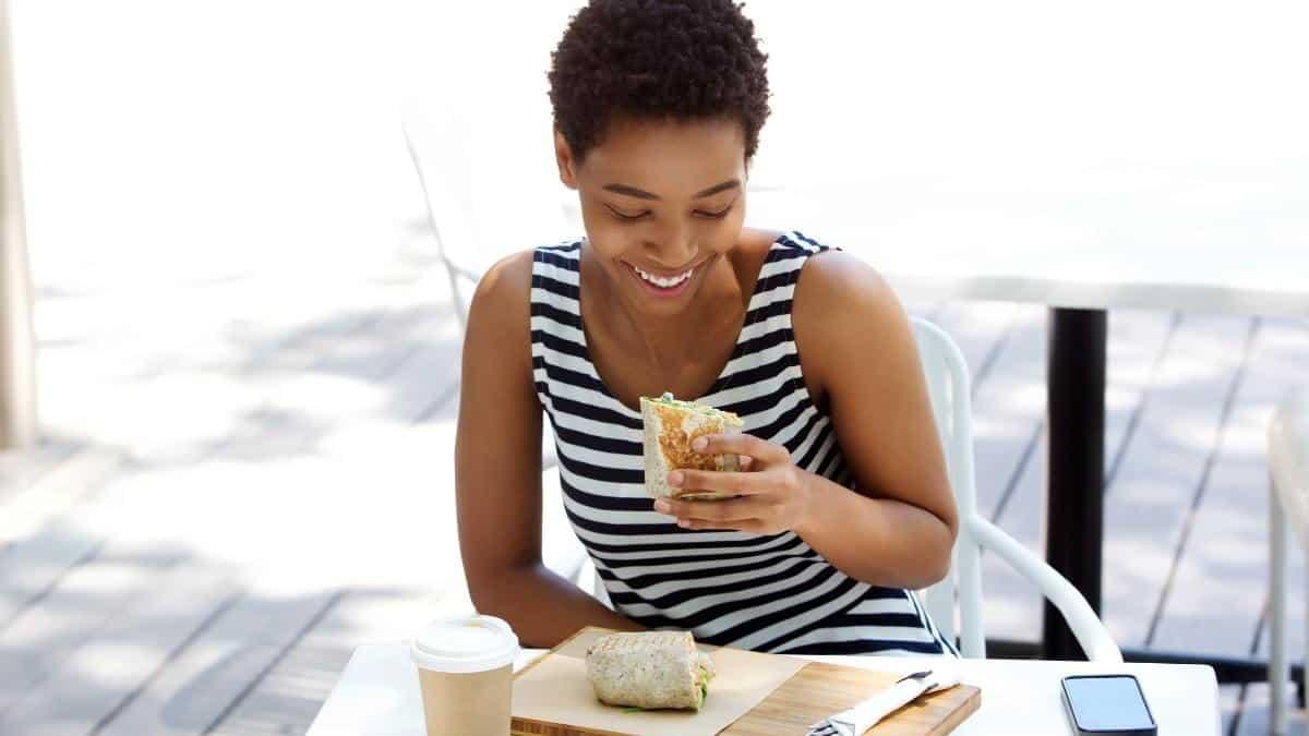 A woman smiling outside enjoying a meal.