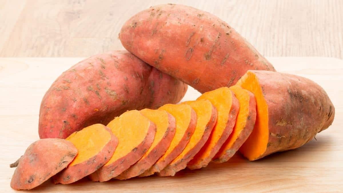 Sweet potatoes whole and sliced on a cutting board, an example of anti-inflammatory foods.