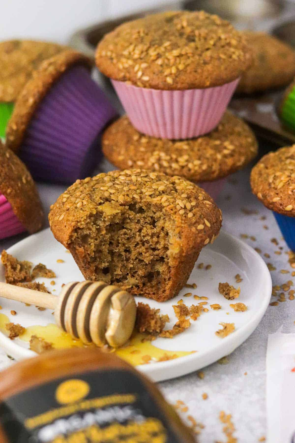 honey flaxseed muffin on a plate with two stacked behind it.