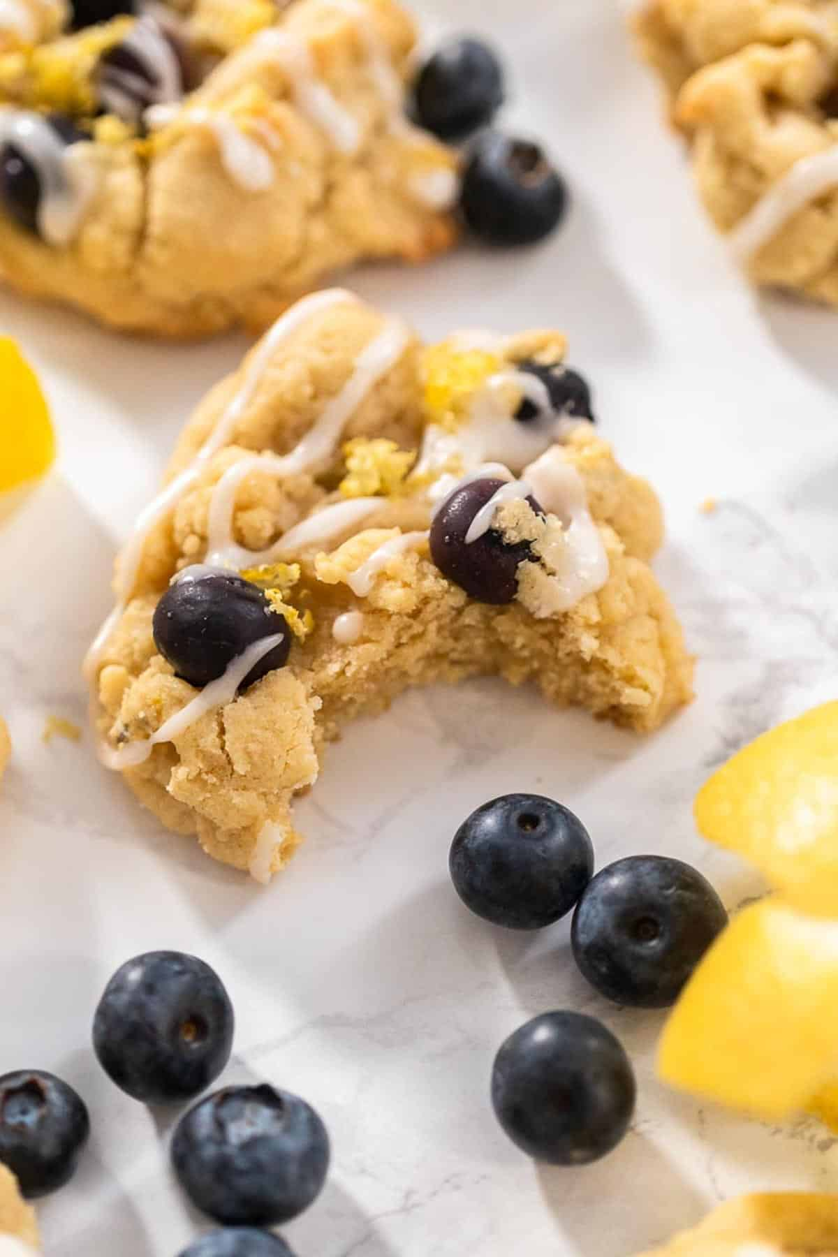 A blueberry lemon cookie with icing drizzled on top surrounded by fresh blueberries and lemon sitting upon a grey and white marbled counter top.