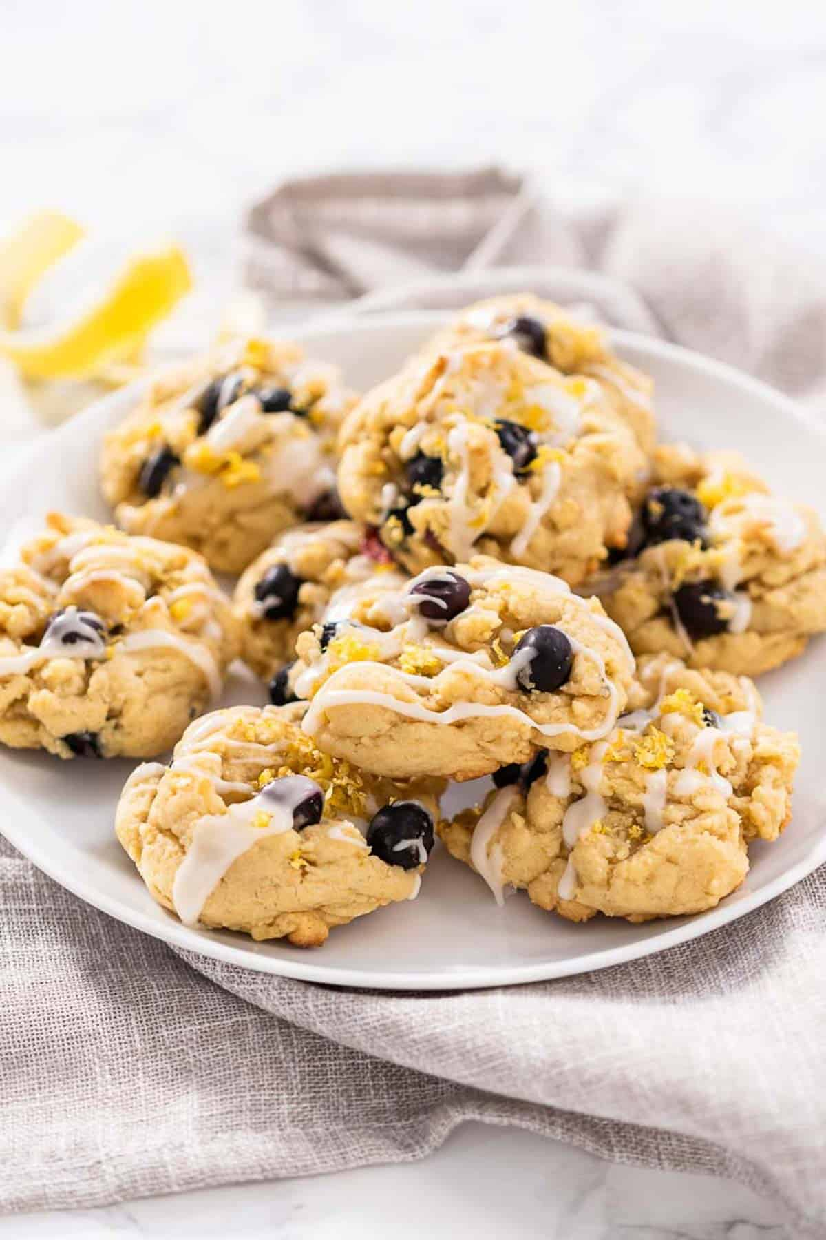 A plate of blueberry lemon cookies with icing drizzled on top sitting upon a grey kitchen towel.
