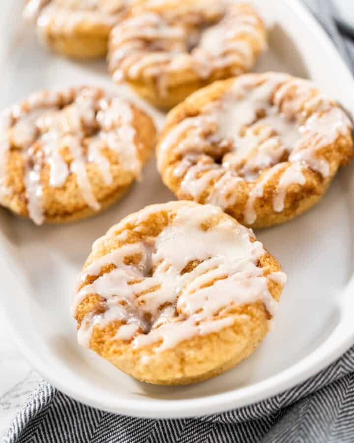 A plate of cinnamon roll donuts with frosting.