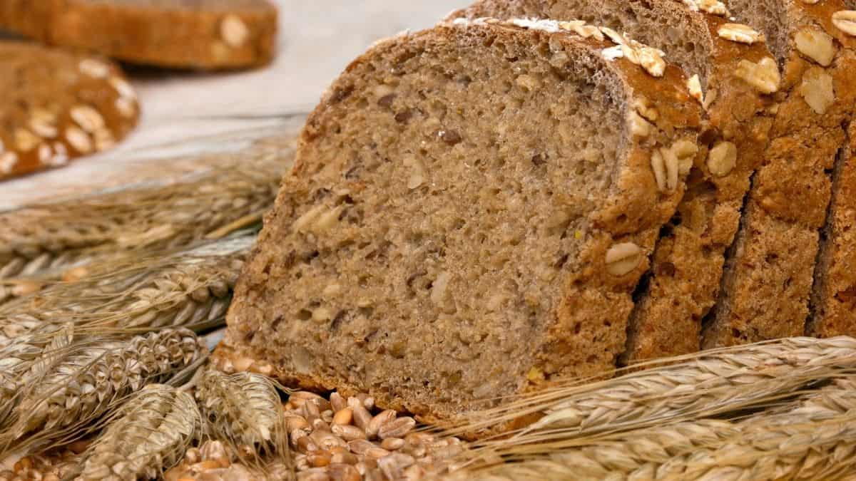 a loaf of whole grain bread surrounded by wheat, an example of a smart carb.