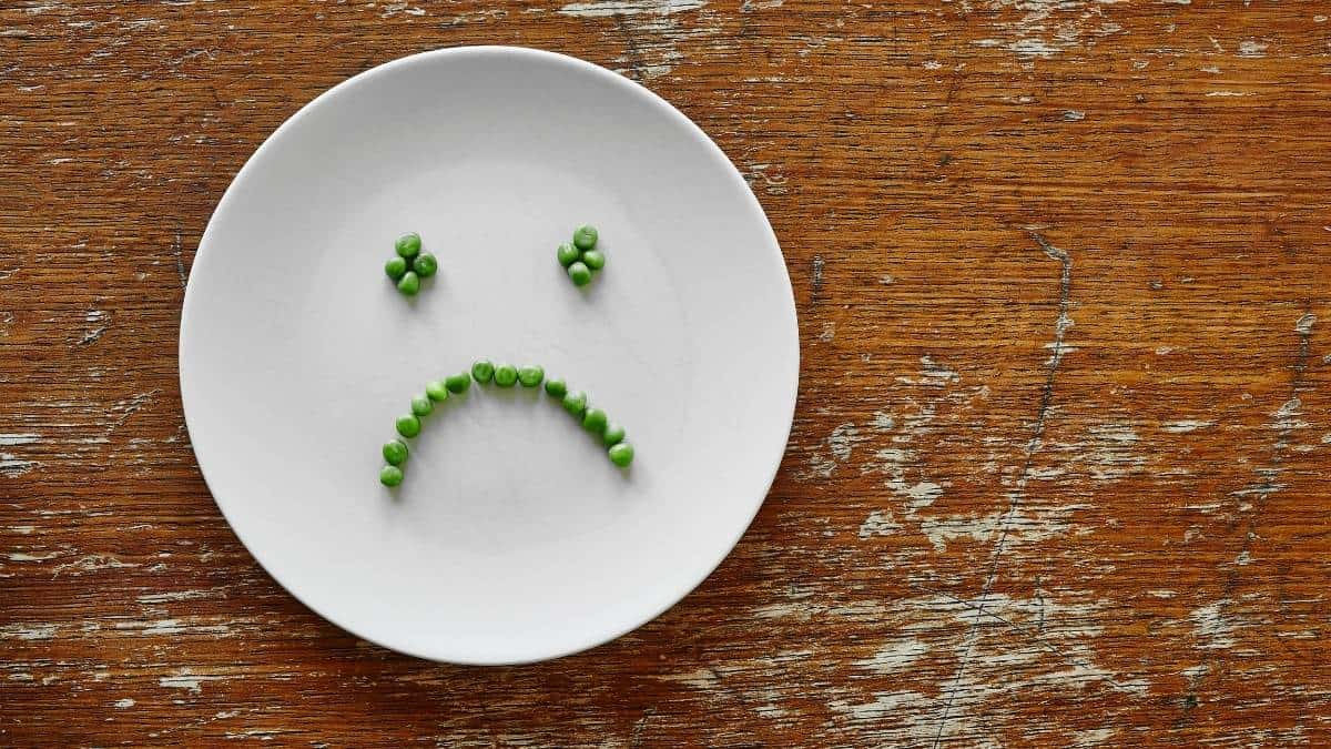 a white plate with a sad face spelled in peas on a wood table.