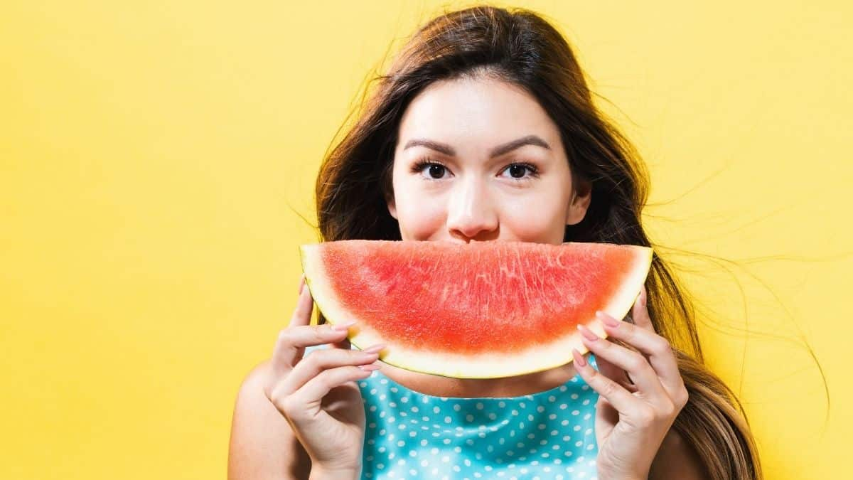 a young woman holding a watermelon slice in front of her face to look like a smile, an example of a restricted food on the slow carb diet.