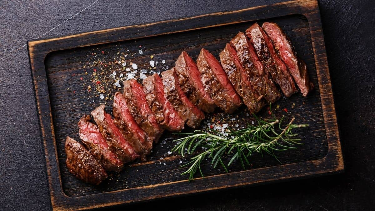 sliced steak with rosemary sprigs on the side on a wooden serving platter, an example of food you can eat on the slow carb diet.