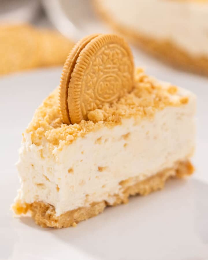 A slice of Golden Oreo Cheesecake with a bite taken out.