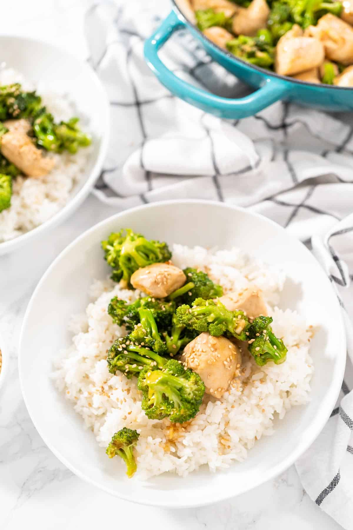 A white bowl filled with white rice and Easy Broccoli Chicken Stir Fry.