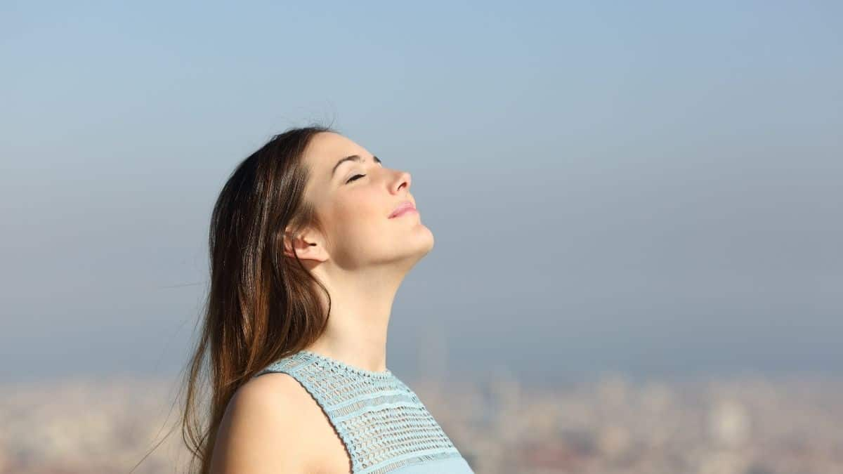 A woman with her eyes closed taking a deep cleaning breath, a way to help lower cortisol levels and anxiety.