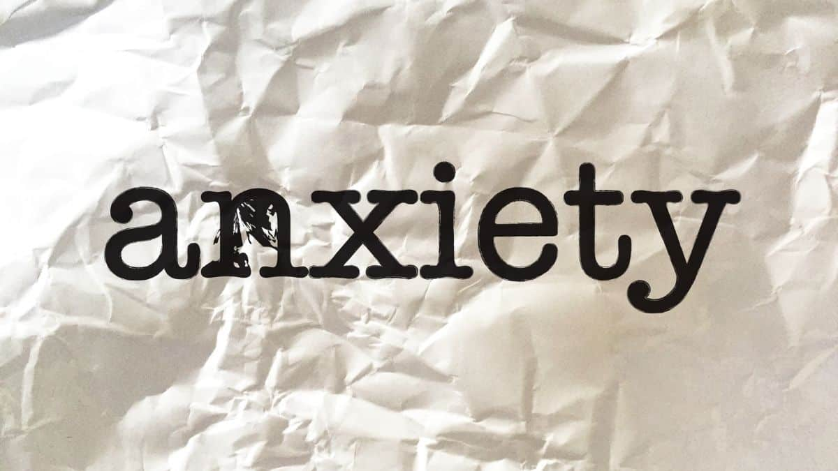 The word anxiety spelled out in black letters on a piece of white crinkled paper.