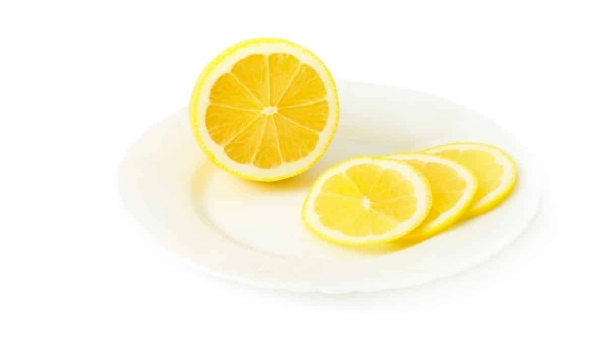 a lemon on a white plate, half of it sliced.