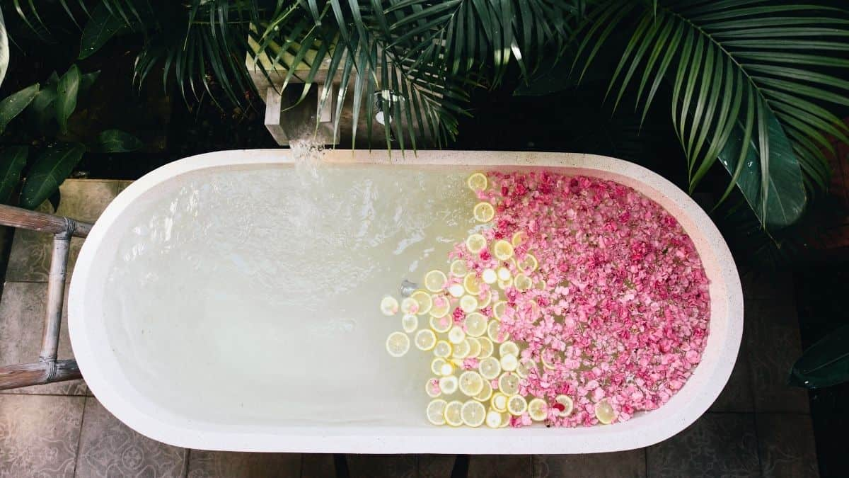 a-white-oval-bathub-filled-with-pink-flower-petals-and-lemon-slices-ready-for-an-emotional-self-care-bath.