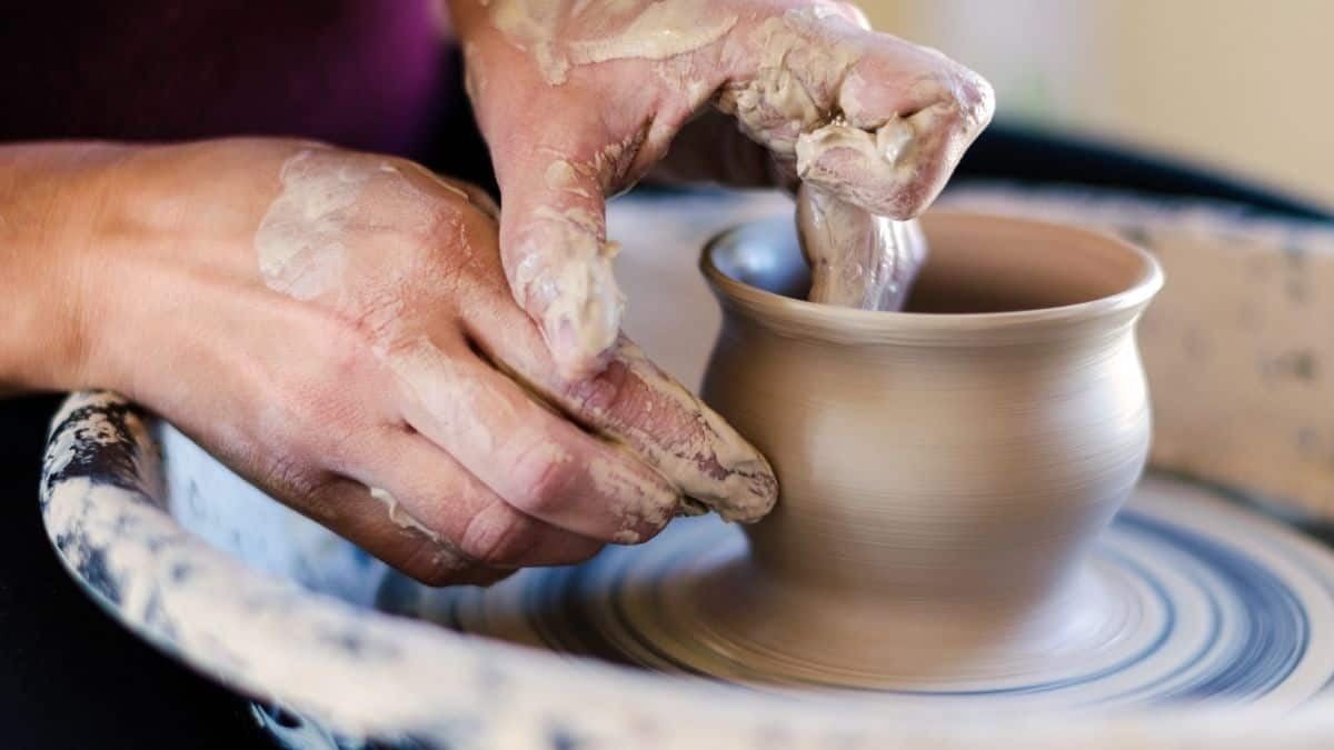 a woman at a potters wheel throwing a clay pot; we see her hands shaping the pot, this is an example of emotional self care.