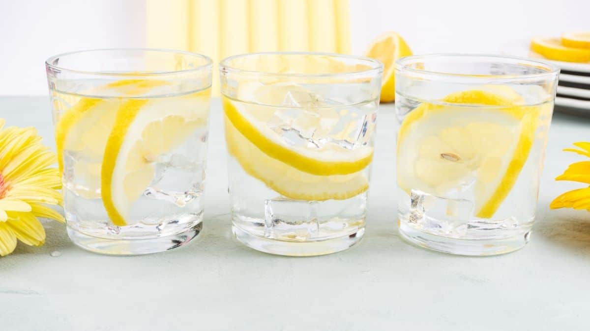 three glasses of lemon water on a table.