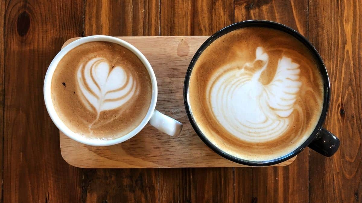 two cups of coffee with latte art, one is larger in a black mug and the other smaller in a white mug, an example of emotional self care.