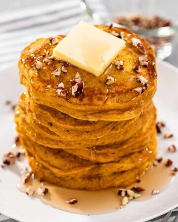 A picture of Bisquick Pumpkin Pancakes with butter, pecans and maple syrup drizzled atop.