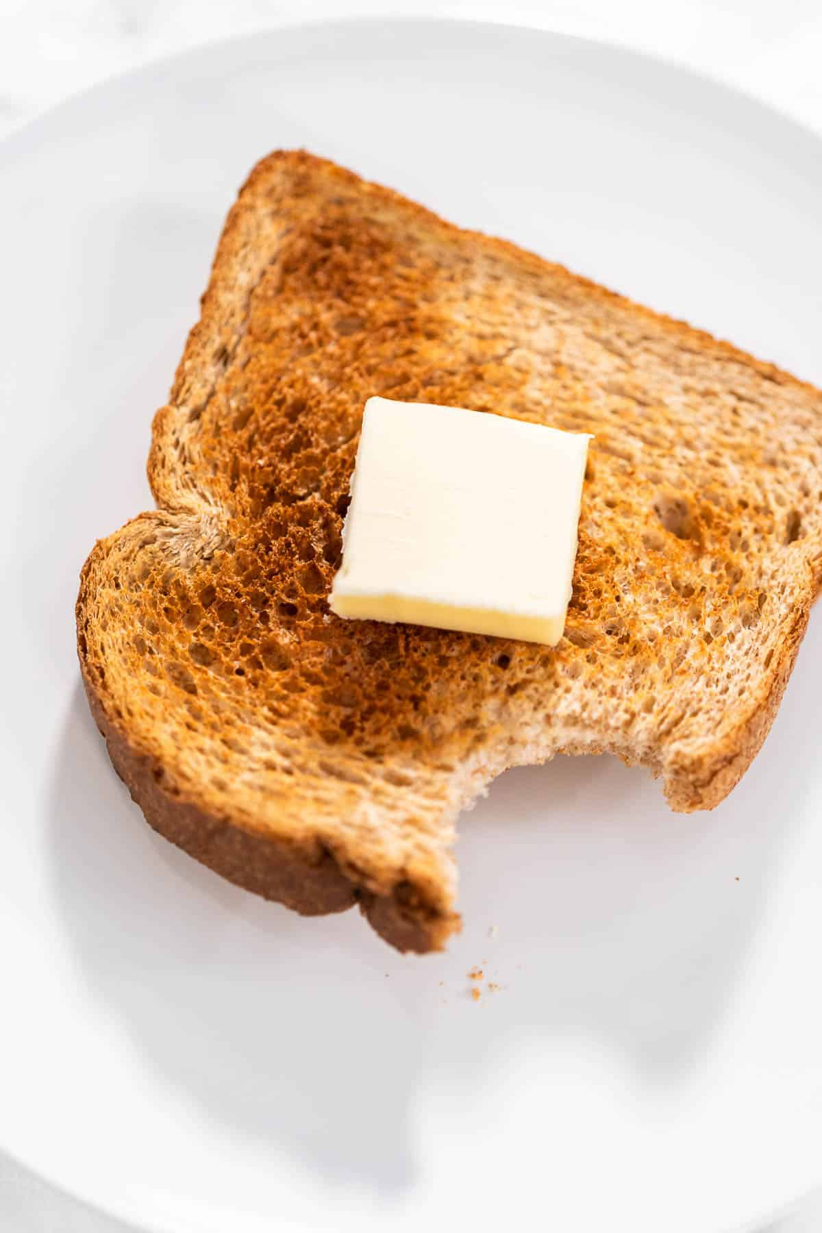 A piece of air fryer toast with a pat of butter on top with a bite taken out of it.
