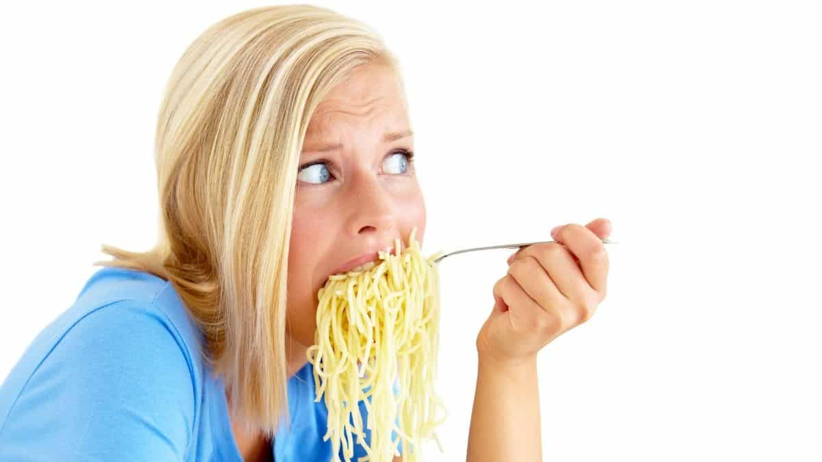 a blonde woman eating a large forkful of spaghetti noodles with a worried look on her face, an example of what a binge could look like.