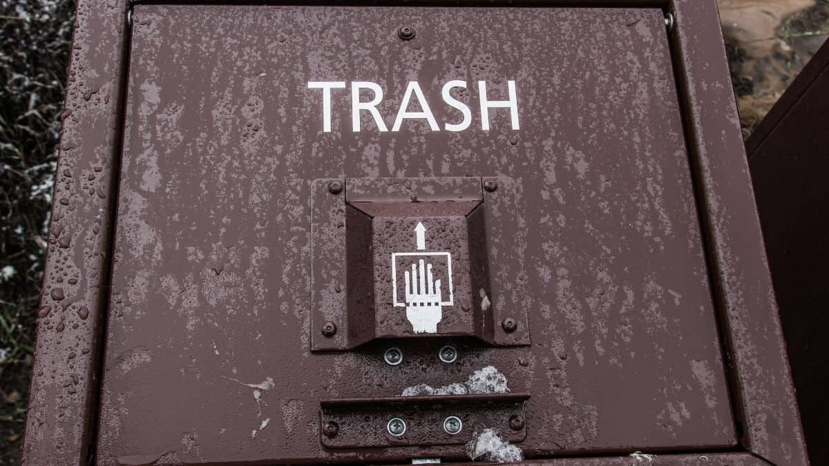 a brown trash can with the word trash spelled out.