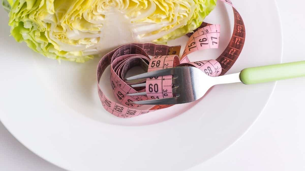 a measuring tape wrapped around a fork on a white plate, a tool a dieter may use.