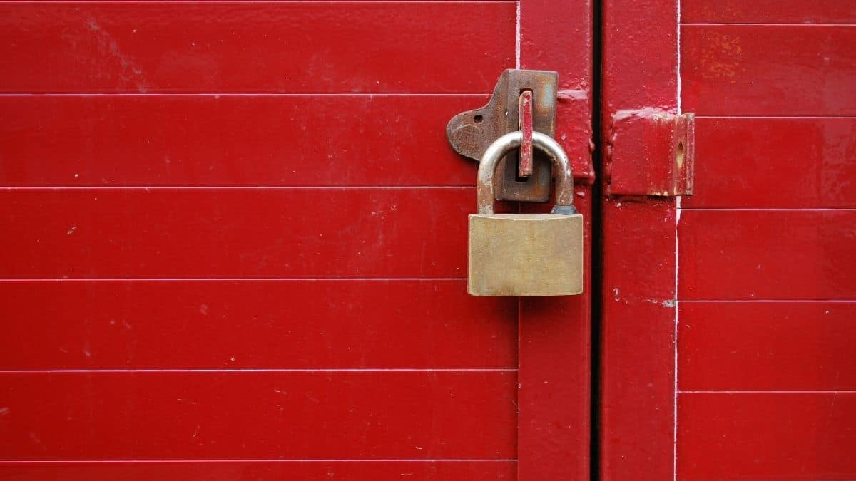 a padlock on a door latch holding a red wooden gate shut.