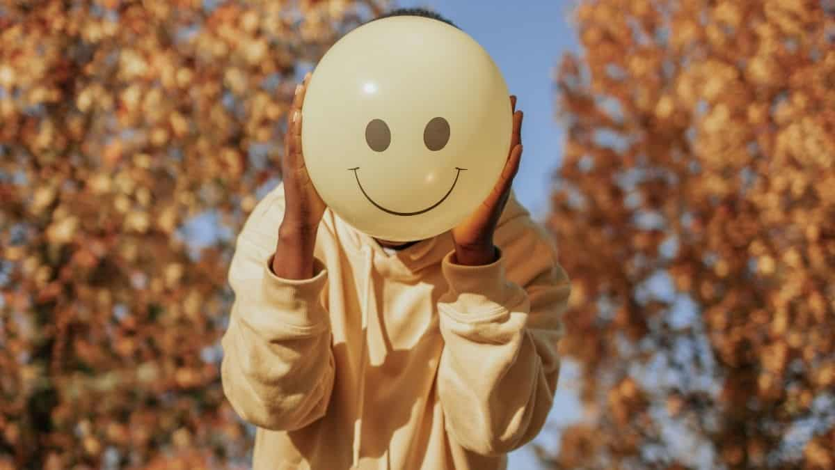 a person holding a smiley balloon in front of their face.
